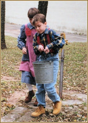 Photograph of Boy Carrying Pail of Water